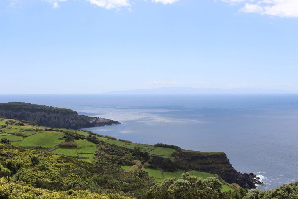 Blick über Wiesen und Klippen auf das Meer