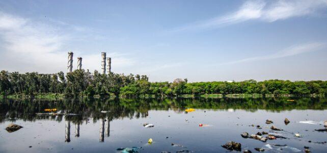 Foto eines mit Plastikmüll verschmutzten Gewässers. Im Hintergrund sind Schornsteine einer Fabrik zu sehen.